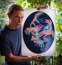 "Scott Hutchison holding a poster of ""Medusa"""